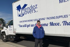 "This image shows a mover in front of a Mendez Movers truck stating ""You will get an Awesome Move""."
