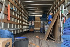 This image shows the inside of a Mendez Movers truck with furniture and boxes.